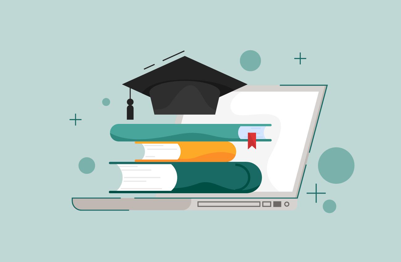 Graduation caps, books and laptop